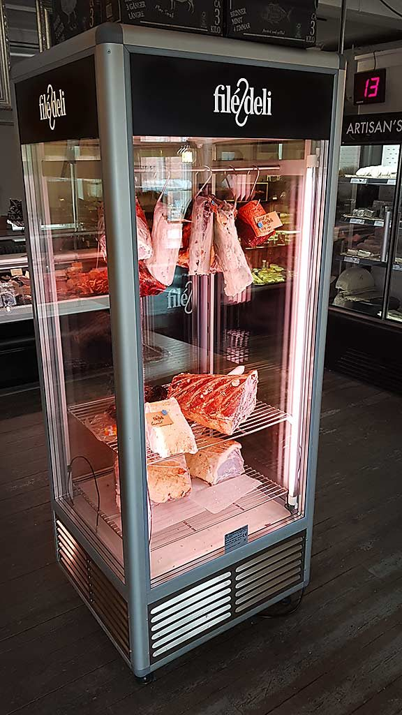 Bild på stor kyl med kött hängandes inuti.
